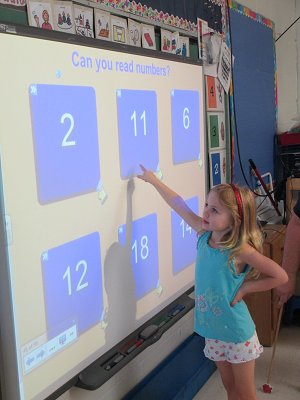 Student picking numbers off a board